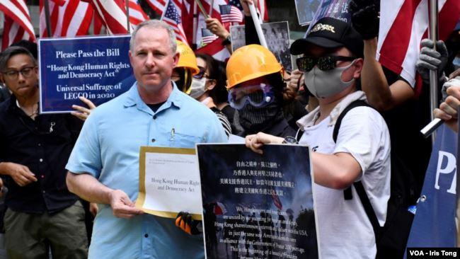 香港抗议者举着星条旗在美国驻港总领事馆前集会,要求美国支持香港民主。领事馆派代表接收游行人士的请愿信及联署宣言。 (2019年9月8日)