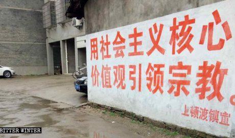 """玫瑰圣母堂附近的墙上写着""""用社会主义核心价值观引领宗教""""的标语"""