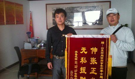 2012年,掌士超律师(左)接受一百余户小区业主赠送锦旗。