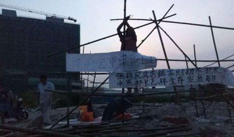 中国广东的一名农民在被拆迁的自家住宅原址搭建竹棚居住