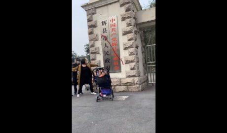 疫苗受害者家长何方美在河南辉县政府牌匾上泼洒红色油漆后被保安带走